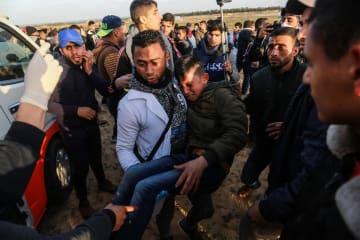 8日、ガザ南部ラファで行われたイスラエルへの抗議デモで負傷したデモ参加者(中央)(ゲッティ=共同)