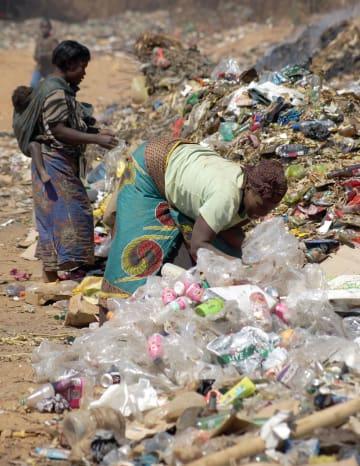 巨大なごみの山の中で、売れる物をあさる貧しい人々。多くの発展途上国では環境破壊と貧困が共に深刻だ=2018年8月、ザンビア・カブウェ近郊(共同)