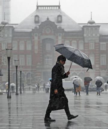雪が降る中、東京駅前を傘を差して歩く男性=9日午前