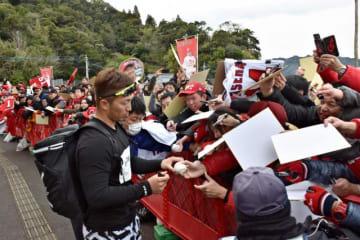 必死に声を掛けるファンにサインをする鈴木誠也選手(左)。気さくに応じてくれるのもキャンプの魅力=9日午後、日南市・天福球場