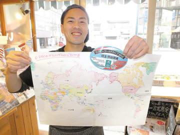 世界地図を手にラグビーロードランニングチャレンジをPRする臼杵健さん