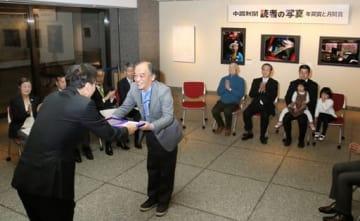 佐藤編集局長(手前左)から表彰盾を受け取る福田さん(撮影・福井宏史)