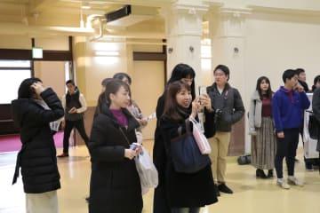 写真を撮りながら見学するモニターツアーの参加者ら=佐世保市平瀬町、市民文化ホール