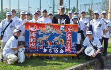 福浦選手(中央)に通算2千安打達成記念の大漁旗を贈ったかもめ会の会員たち=9日、沖縄県石垣市