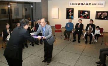 佐藤編集局長(手前左)から表彰盾を受け取る福田さん