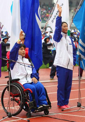 力強く宣誓する(右から)田井選手、立川選手=県立総合運動公園陸上競技場