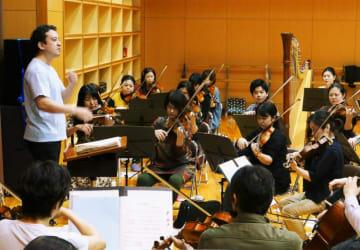 稽古に取り組む指揮者の柴田真郁さん(左端)と琉球交響楽団のメンバー=8日、浦添市てだこホール練習室