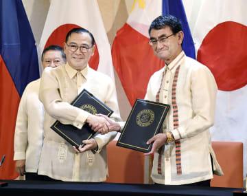 フィリピン・ダバオでの共同記者発表を前に、ロクシン外相(左)と握手する河野外相=10日(共同)
