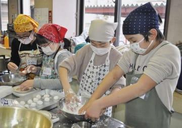 【協力して菓子作りをする児童=津市寿町の敬和公民館で】