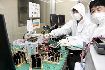 打ち上げを目指す超小型人工衛星の性能を確かめる中城智之教授(右)ら=福井県の福井工大福井キャンパス
