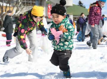 雪の中からお菓子などを探す子どもたち