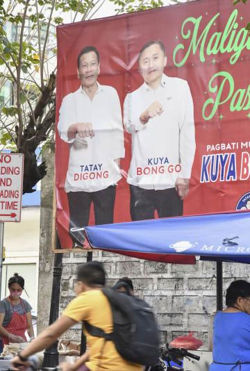 フィリピン・マニラで掲げられた、ドゥテルテ大統領(左)と前大統領特別補佐官のゴー氏が並んだ横断幕=12日(共同)