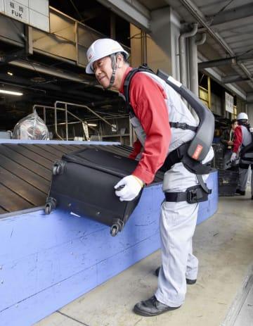 日航が導入した「パワードウエア」を装着して荷物を取り扱う担当者=12日午後、羽田空港