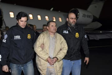 移送されるホアキン・グスマン被告(中央)=2017年1月19日、米ニューヨーク州(米司法当局提供、AP=共同)