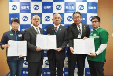 協定書を手にする本山町長(中央)とコンビニ関係者