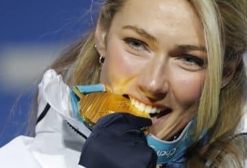 2018年2月、平昌冬季五輪のアルペンスキー女子大回転で優勝し、表彰台で金メダルをかじるミカエラ・シフリン(ロイター=共同)
