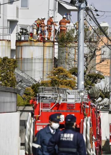 男性2人が転落した工場のタンクの上で、作業する消防隊員ら=13日午後1時16分、大阪府和泉市