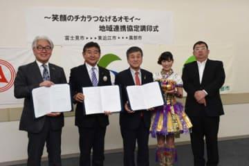 調印書にサインした小椋正清市長(左から2人目)ら3市の市長と「ももいろクローバーZ」の高城れにさん(左から4人目)=埼玉県富士見市役所、東近江市提供