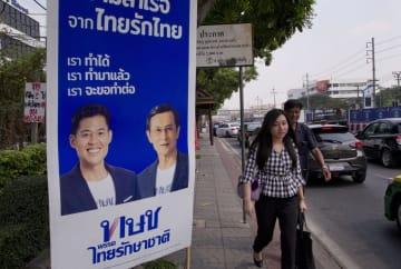 13日、バンコクで、タイ国家維持党のポスターの近くを歩く通行人ら(AP=共同)