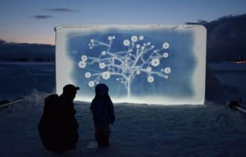 雪の壁に照らし出された作品。手前のスイッチを踏むと、映像が投影される