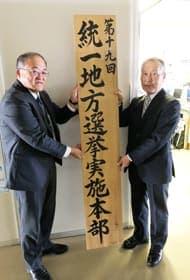 統一地方選実施本部の看板を掲げる今成本部長(左)と三浦選管委員長