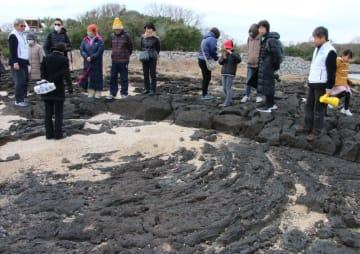 流れた溶岩が縄を束ねたように冷え固まっている様子(手前)を観察する参加者=五島市