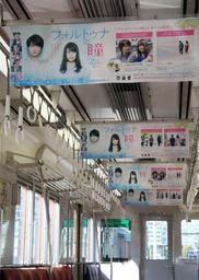 映画「フォルトゥナの瞳」をPRするため、中づりポスターが並ぶ阪神電鉄の車内=尼崎市北城内
