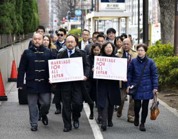訴状を提出するため、東京地裁に入る原告団ら=14日午前、東京・霞が関