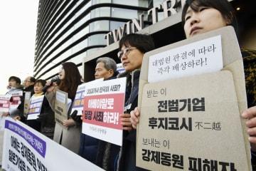 14日、ソウルの日本大使館前で集会を開いた市民団体のメンバーら(共同)