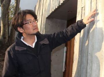 山荘わらび野の営業をあす再開する高田陽平さん。旅館のコンクリート外壁は周辺の自然となじむよう木目調にした=由布市湯布院町川北