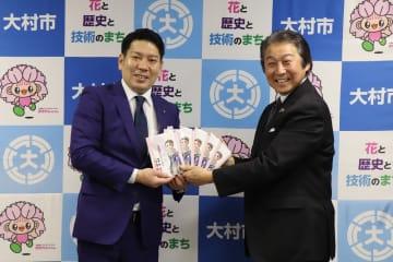 園田市長に石井筆子の漫画を寄贈する酒井理事長(右)=大村市役所