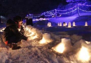 ろうそくの明かりの幻想的な雰囲気を楽しむ参加者=柏崎市西長鳥の岩之入集落