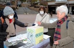 模擬投票に1票を投じる参加者(右)=兵庫県尼崎市神田中通1