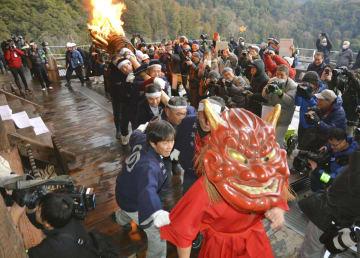 奈良県桜井市の長谷寺で行われた伝統行事「だだおし」で、大たいまつを伴い参拝者らを威嚇する赤鬼=14日午後