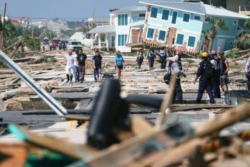大型ハリケーンの被害が出た米フロリダ州の大通りを歩く住民ら=2018年10月11日(ロイター=共同)