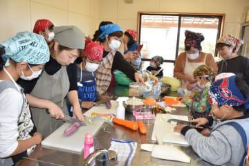 縄瀬の食材を使ってみそ汁を作る交流イベントで、児童に手本を示す川野さん(左から2人目)