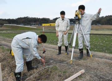 手ぶりを交え声を掛けながら道路幅を測る生徒=鹿屋市川西町