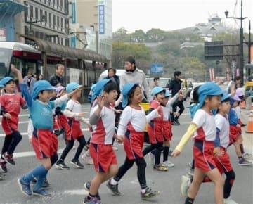 復旧工事が進む熊本城(右奥)を横目に、復興ファンランコースを元気よく歩く園児たち=熊本市中央区