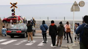 車道に出て、写真を撮影する観光客の姿が目立つ江ノ島電鉄鎌倉高校前駅近くの踏切=鎌倉市内(一部画像を修整しています)
