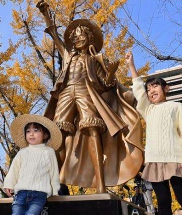 県庁プロムナードに設置された漫画「ワンピース」の主人公ルフィの立像と一緒に記念撮影する子ども=18年11月、熊本市中央区(高見伸)