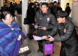 京都サンガFCの選手らが開幕戦のPRチラシを配布した(京都市下京区)