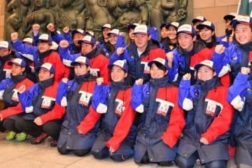 活躍を誓い、結団式で拳を突き上げる本県の選手たち=札幌市内の宿舎
