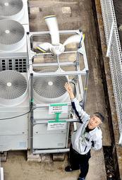 会社敷地内の室外機に風力発電の試作品を取り付けて実証実験に取り組むパイオニア精工の高尾利幸さん=姫路市花田町加納原田