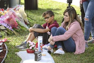 銃乱射事件の現場となった高校前の花壇を見つめる人たち=14日、米フロリダ州パークランド(共同)