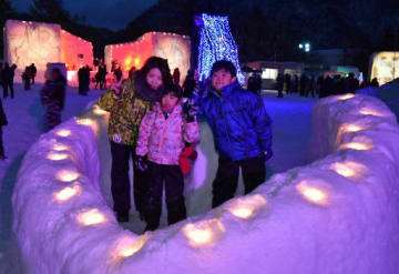 ライトがともるハート形のオブジェで記念撮影する家族