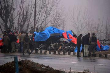 15日、インド北部ジャム・カシミール州の現場で、攻撃を受けたバスの残骸を調べる当局者(ロイター=共同)