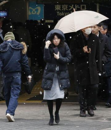 JR新橋駅前で雪が舞う中、歩く人たち=15日午後