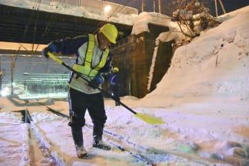 線路を切り替えるポイントを除雪する作業員=14日午前0時45分ごろ、JR小樽駅構内