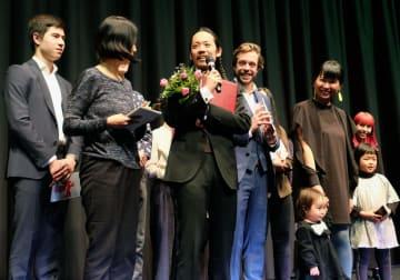 特別表彰を受け、授賞式であいさつする長久允監督(中央)=15日、ベルリン(共同)