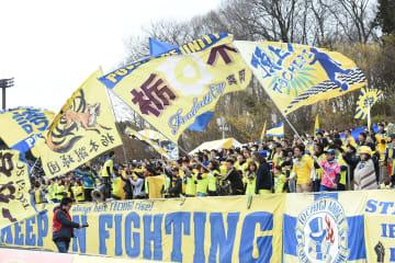 「栃木」の旗を振り、選手に声援を送る栃木SCのサポーター=昨年2月25日、大分との開幕戦より